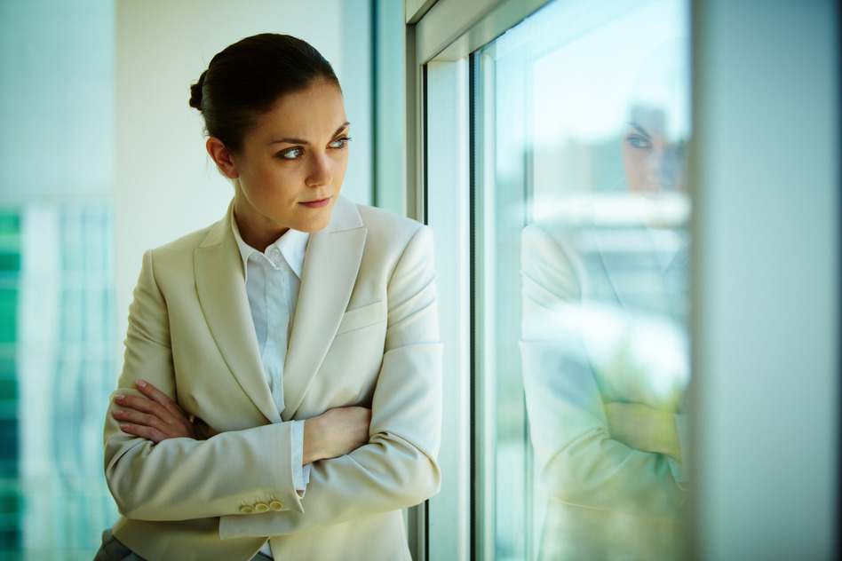 Portrait of serious businesswoman looking through the window in office