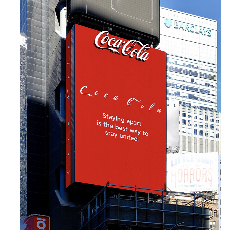 "A huge Coca-Cola billboard in Times Square that reads ""Staying apart is the best way to stay united."