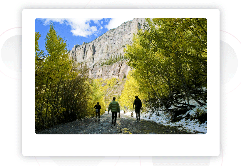 Three people and two dogs on a hiking trail in Aspen, Colorado with snow strewn throughout.