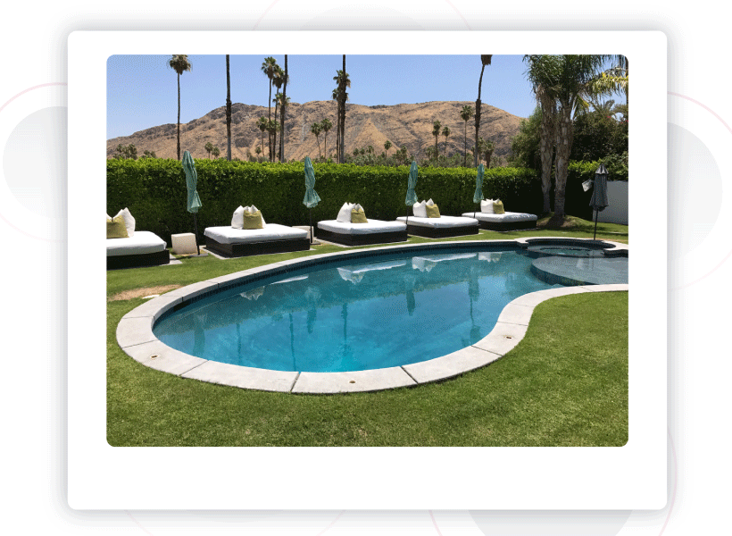 A rounded pool and poolside beds at a home rental in Palm Springs, Ca.