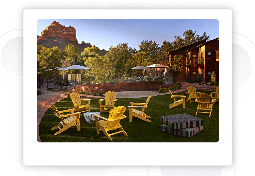 Yellow Adirondack chairs on the grass overlooking red rock formations in the distance.